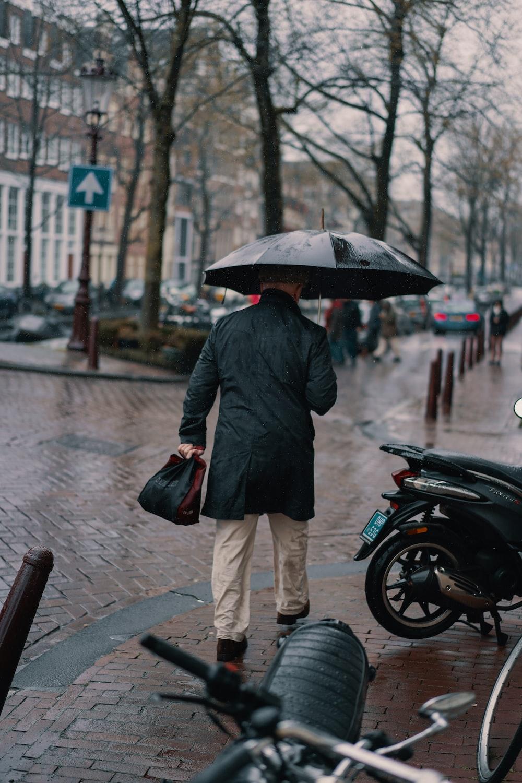 man holding black umbrella