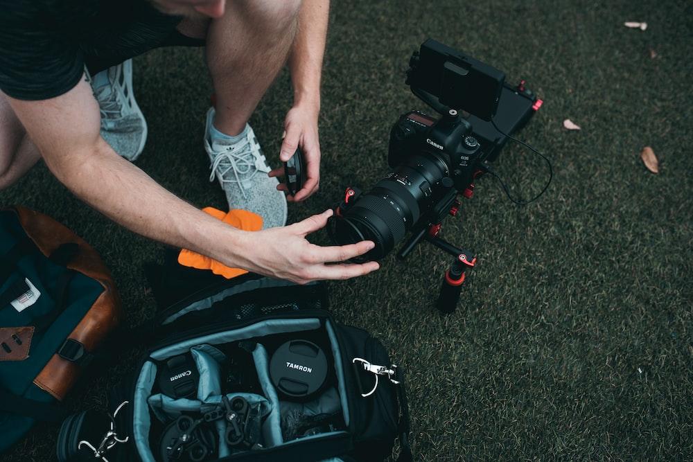 man setting up camera zoom lens