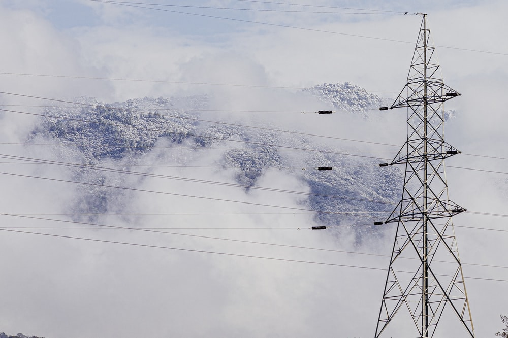 gray transmission tower near mountain during daytime