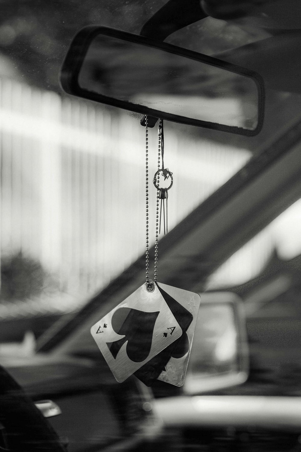grayscale photography of playing card hanging on vehicle rear view mirror
