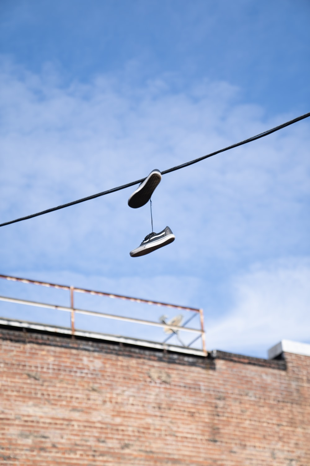 low-angle photography of shoes hanging on cable