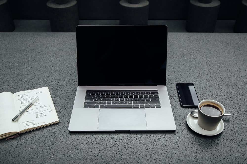 turned-off MacBook Pro between cup of coffee, iPhone, notebook, and pen