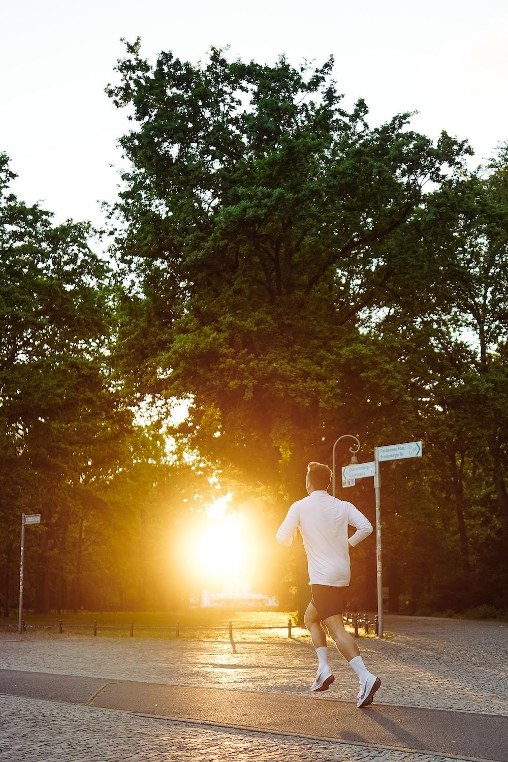 man in running on pathway near trees