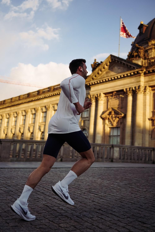 man running near concrete building during daytime