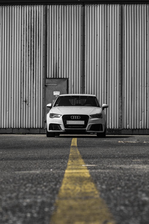 white Audi vehicle on road