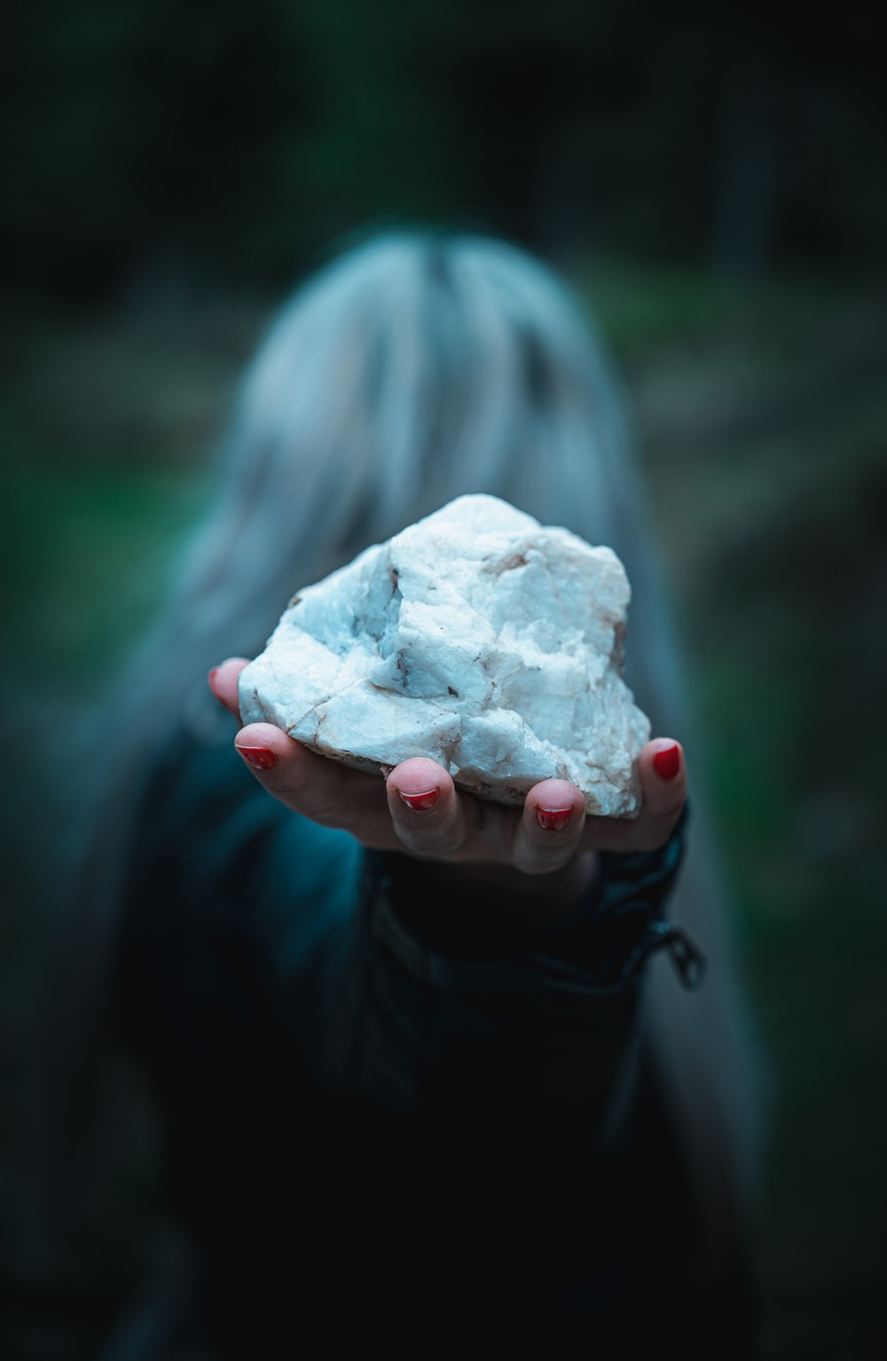 shallow focus photography of unknown person holding white stone
