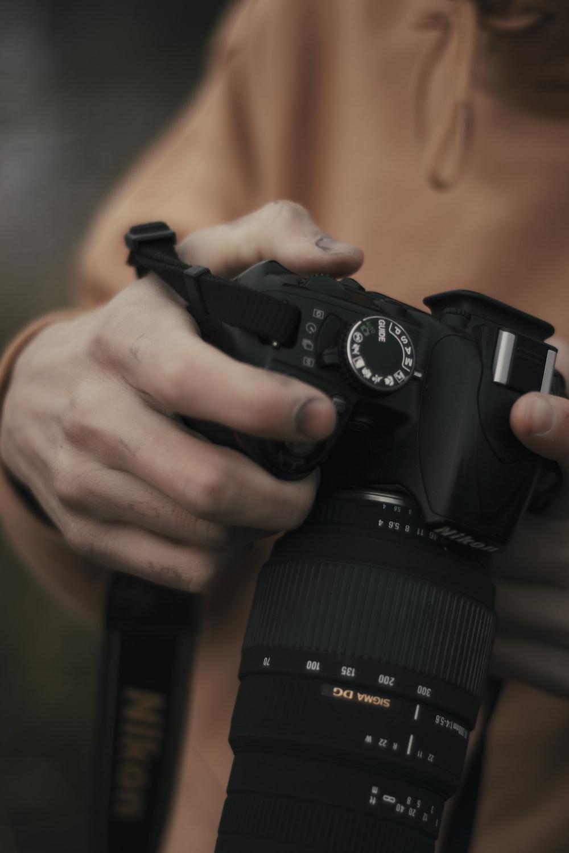 man with black DSLR camera