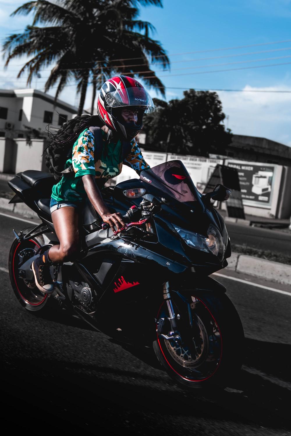 woman wearing green shirt riding on sports bike