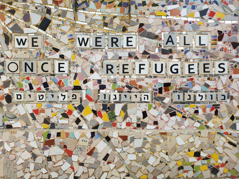 we were all once refugees text on multicolored ceramic tile