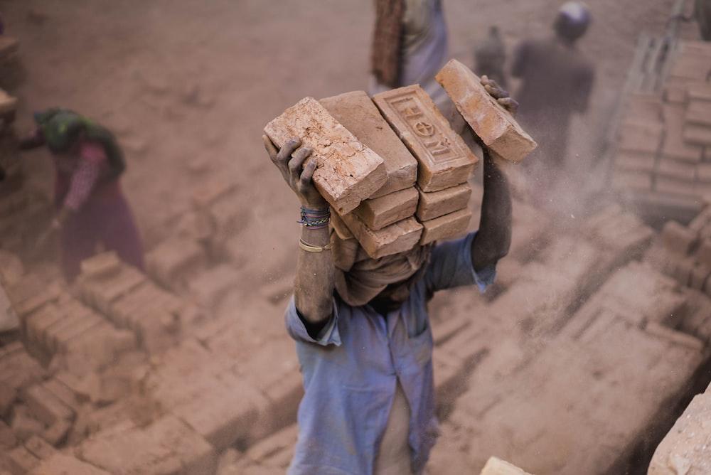man in blue shirt carrying blocks on head