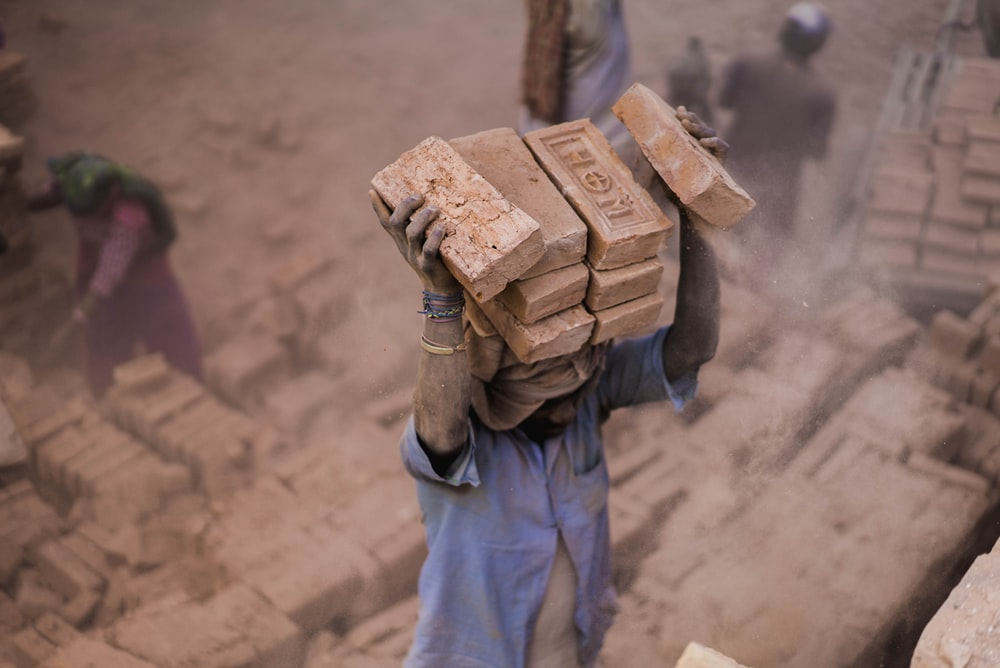 man in blue shirt carrying blocks on head