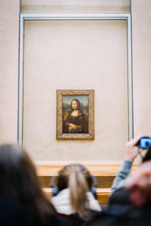 people facing Mona Lisa painting hung on wall inside room