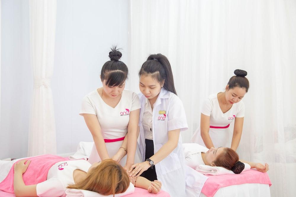 three women standing beside bed