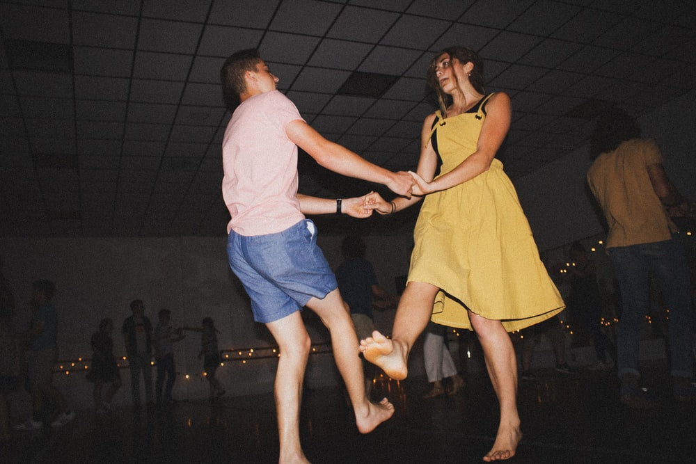 woman in yellow dress dancing with man in white t-shirt