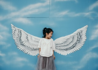 girl leaning on wall with wings mural painting