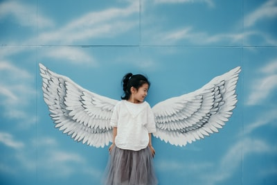 girl leaning on wall with wings mural painting angel teams background