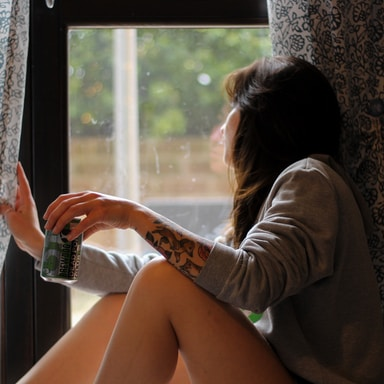 shallow focus photo of woman in gray long-sleeved shirt beside window
