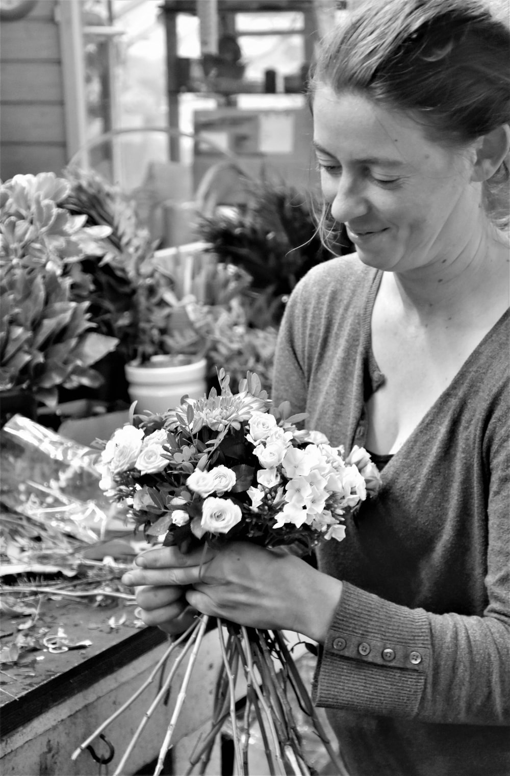 greyscale photography of man arranging flowers