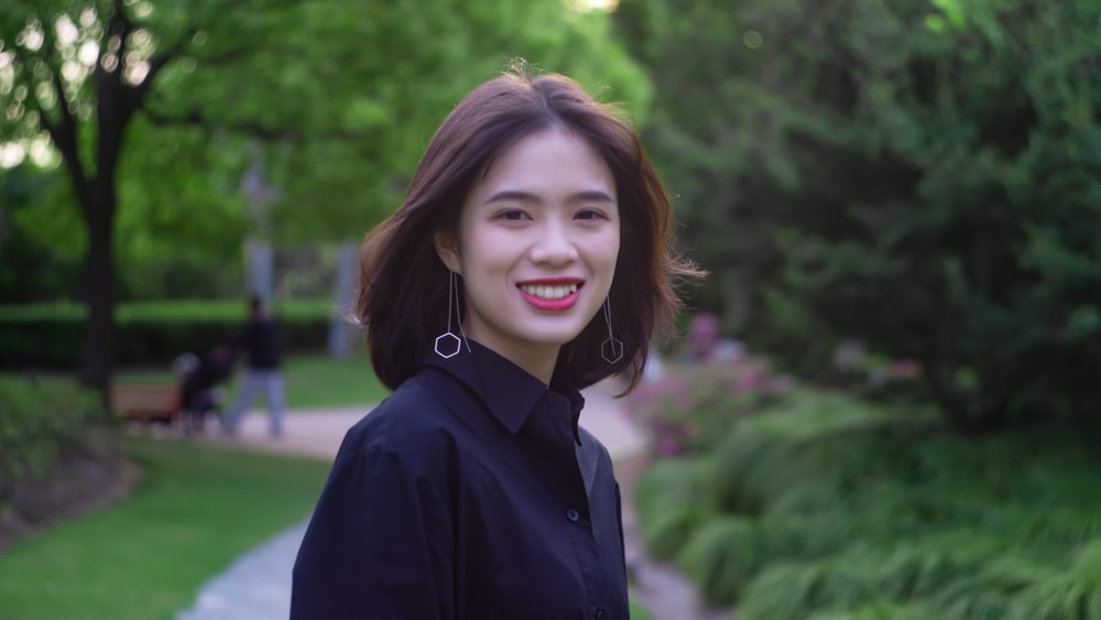 smiling woman wearing black collared blouse