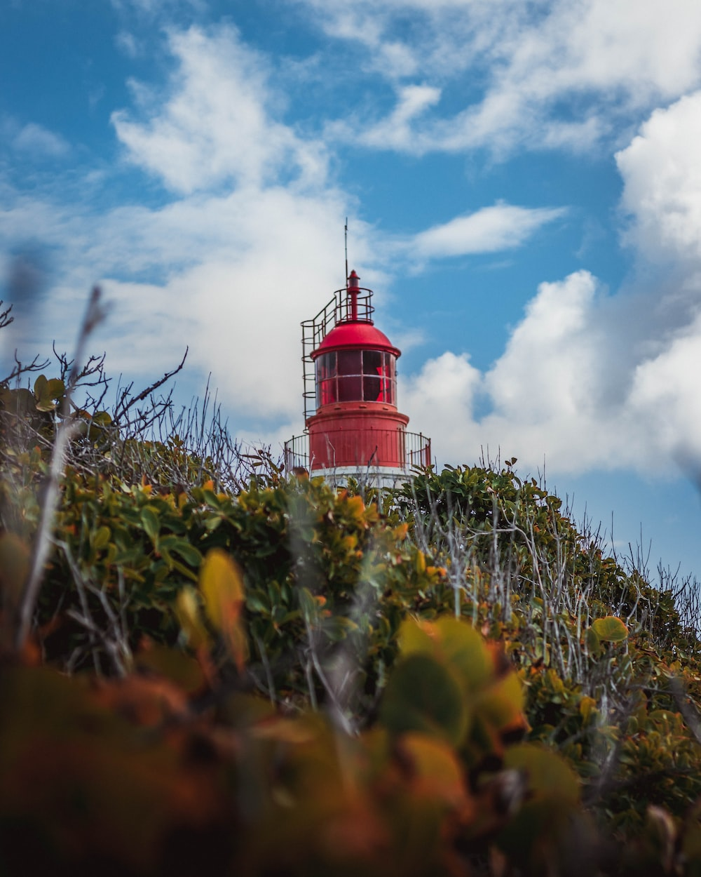 low-angle photography of red tower under blue sky and white clouds