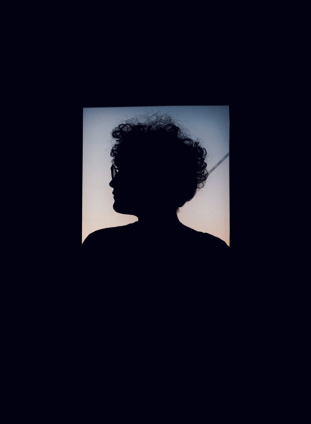 silhouette of person with curly hair and eyeglasses