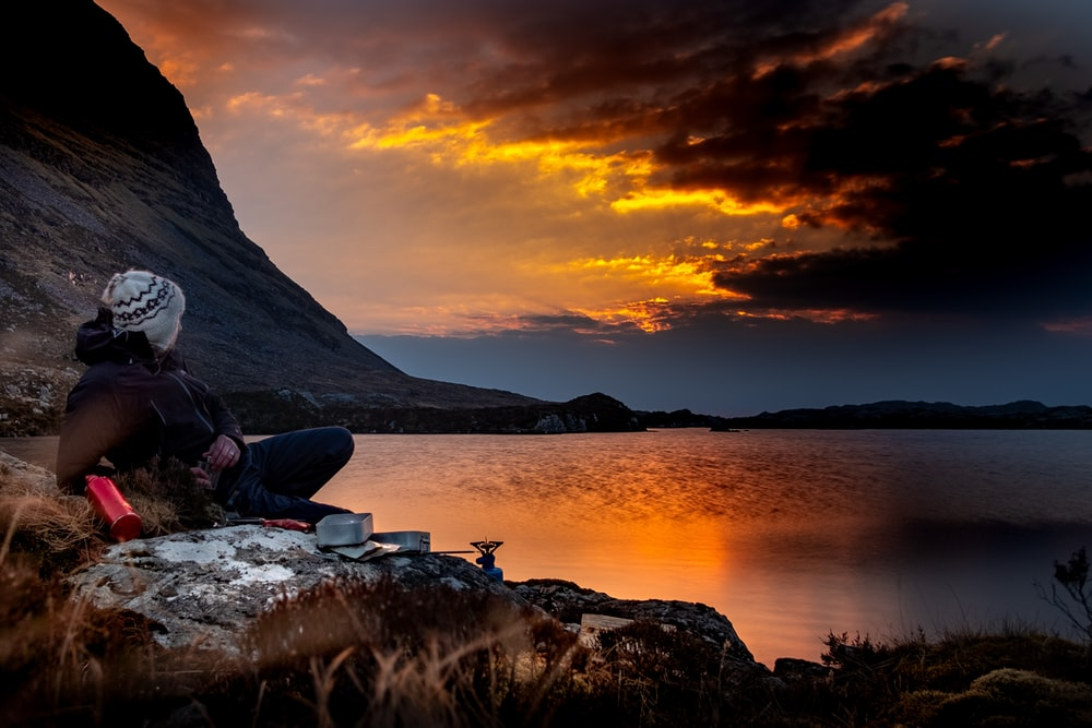 person sitting on cliff facing body of waterr during golden hour