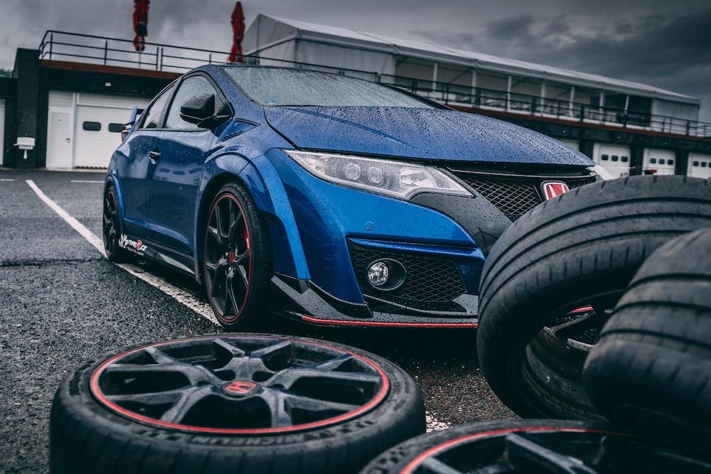 blue Honda vehicle beside vehicle wheel and tire set