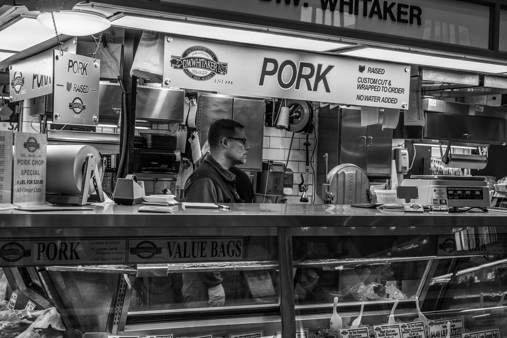 grayscale photography of man inside pork food counter