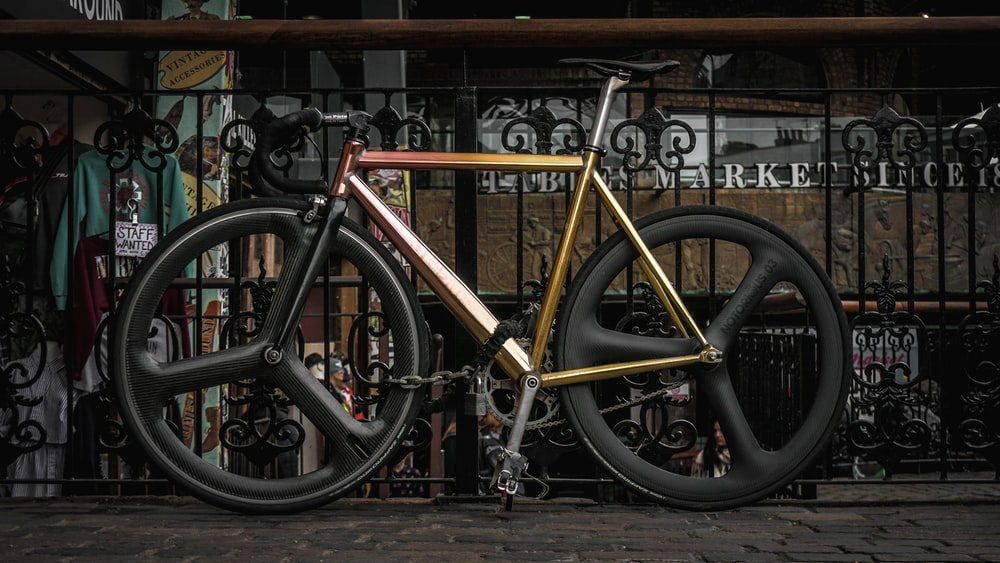 brown road bike leaned on gray metal railings