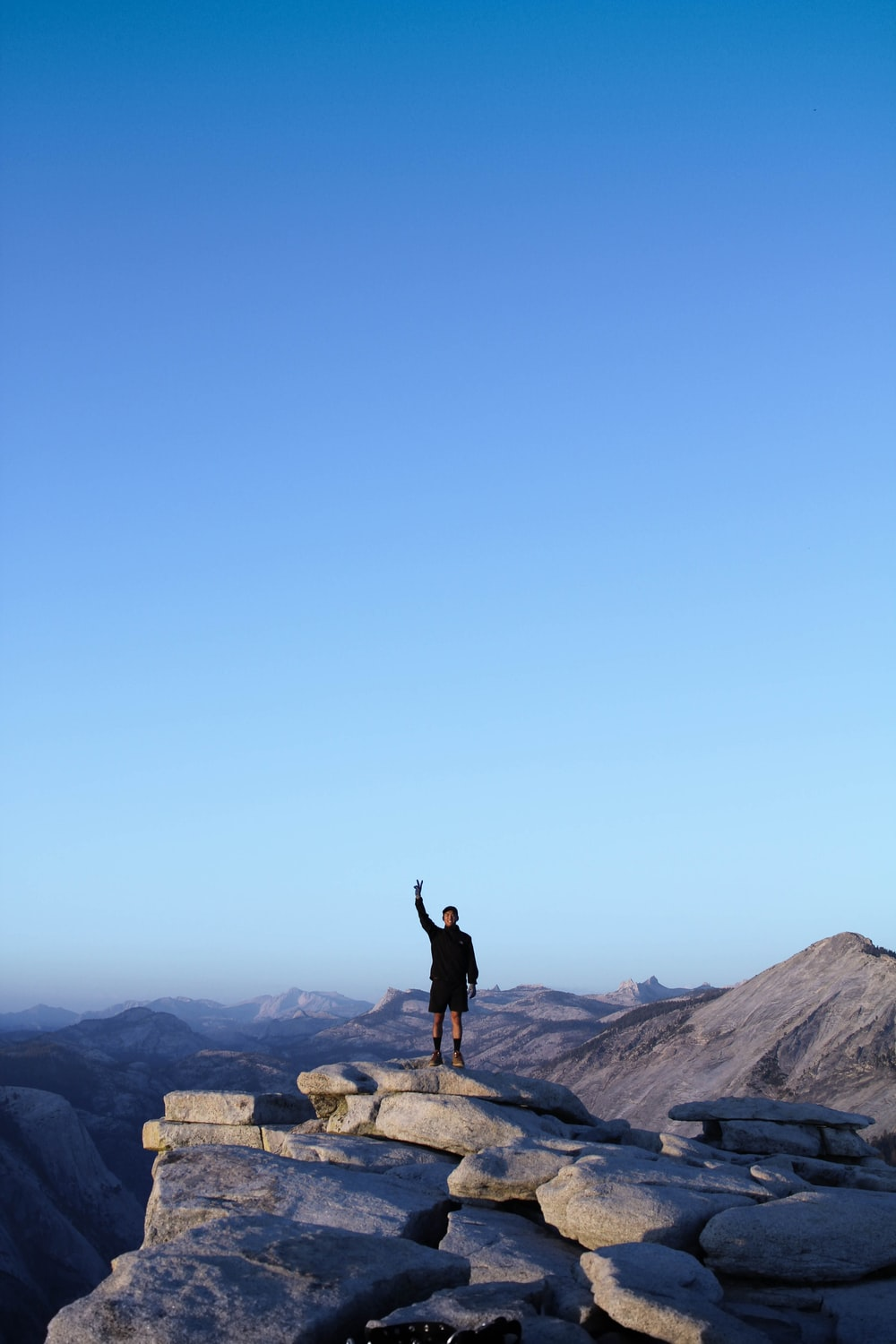 person standing on rocky cliff photography