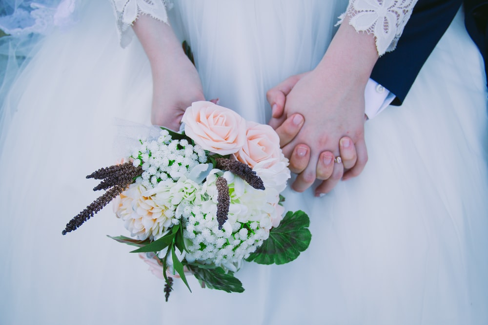 person wearing wedding dress holding bouquet