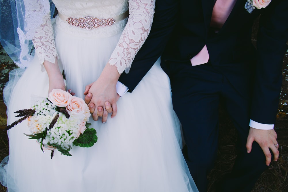 bride and gold holding hands while sitting