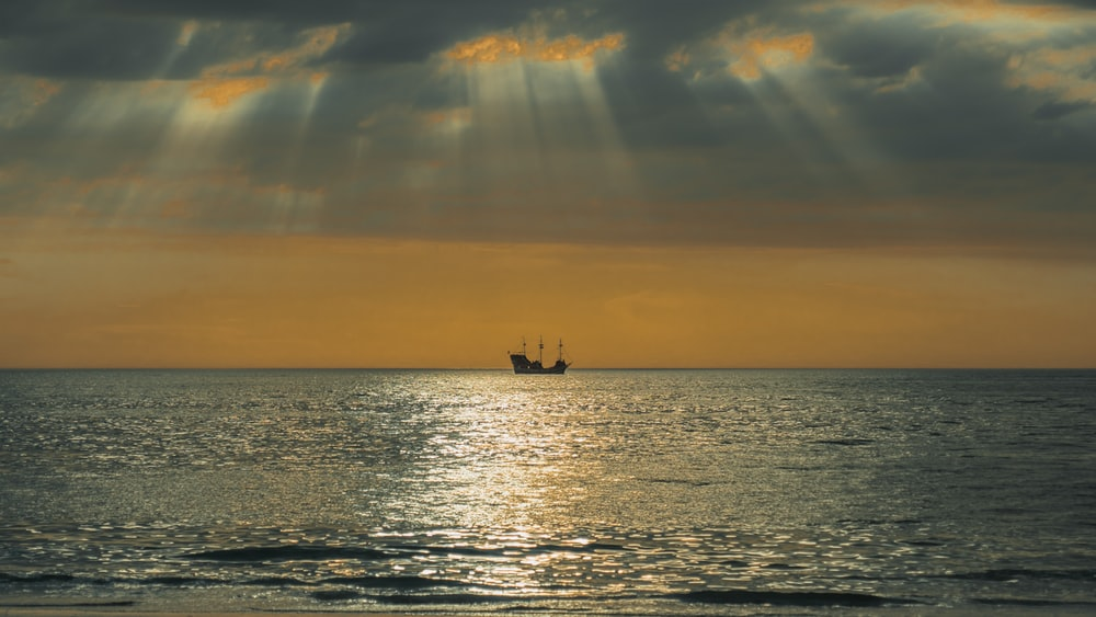 silhouette of boat sailing on sea during golden hour