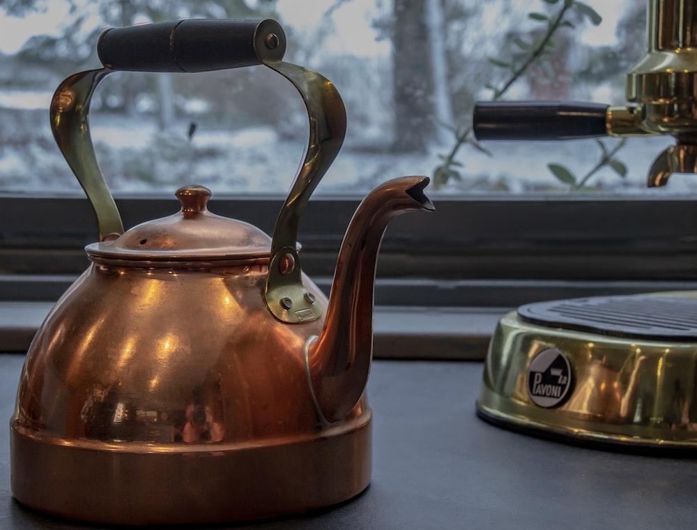 copper kettle and brass espresso machine near glass window