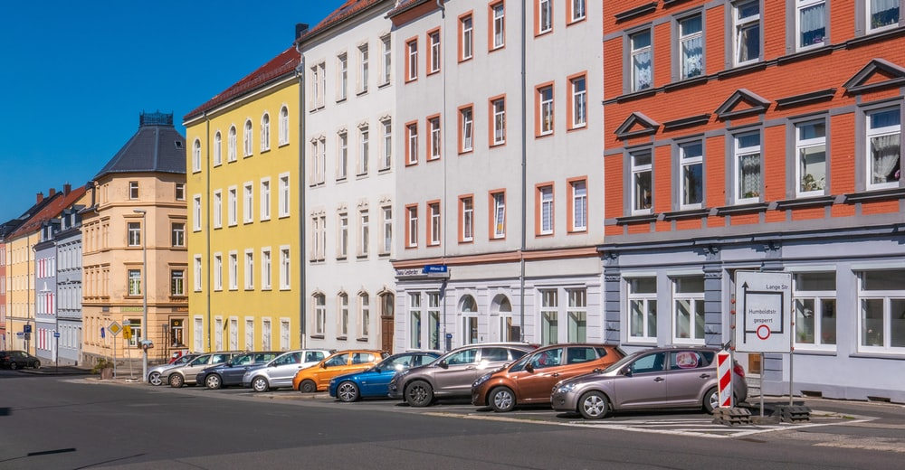 assorted-color cars parked beside apartments