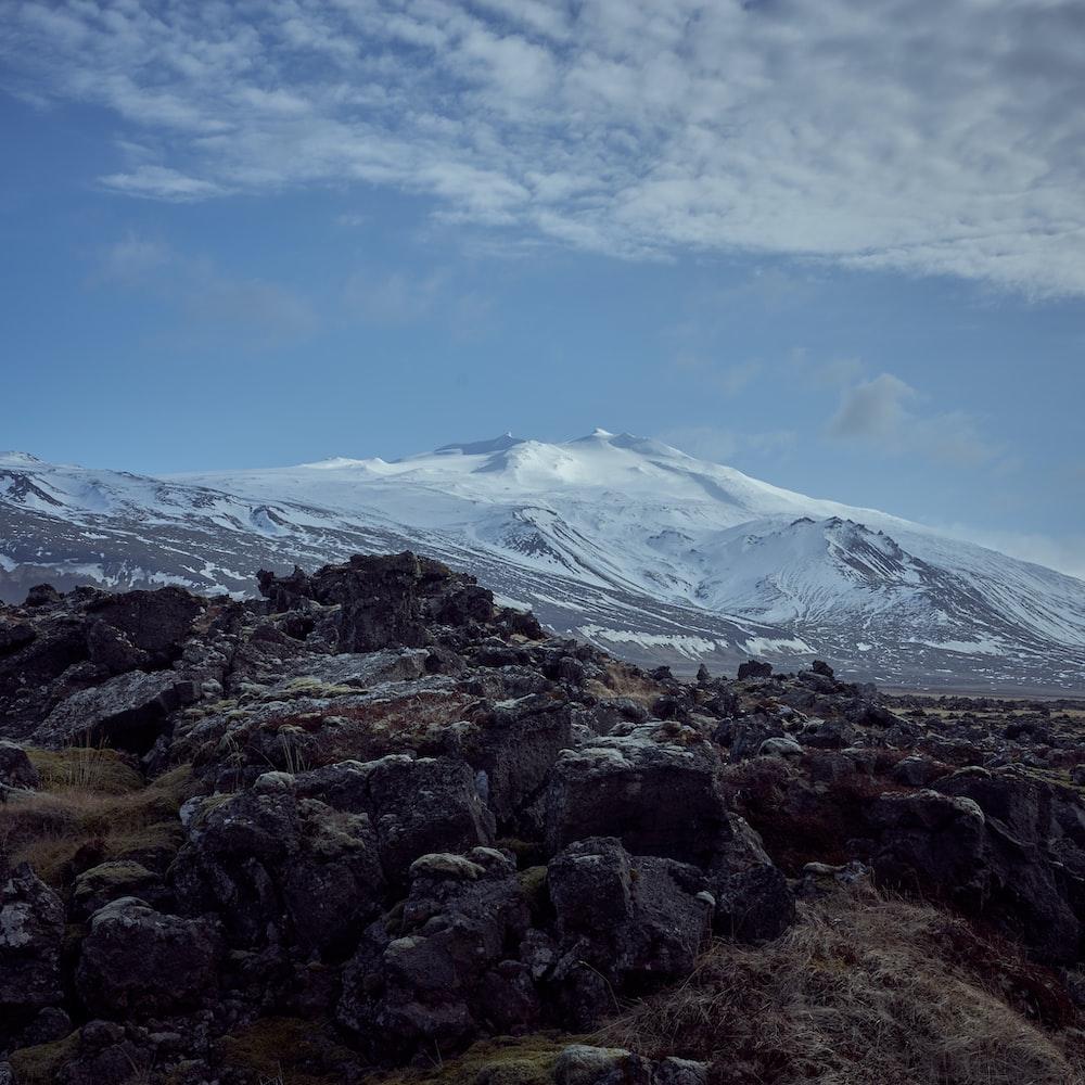 rocky hilltop near white snow capped mountain range