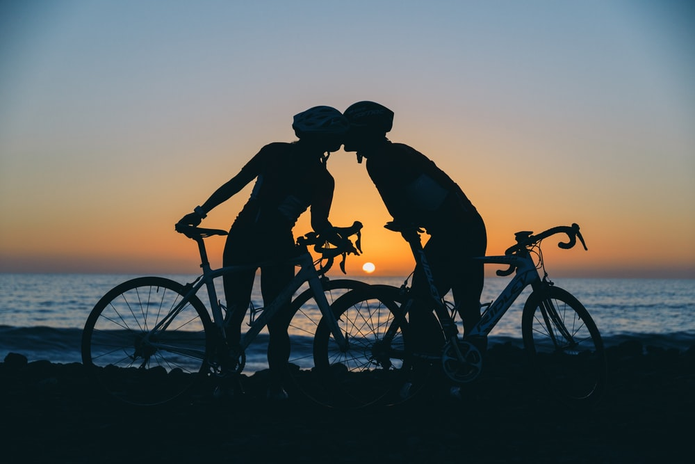 silhouette photography of two people on standing seashore near bikes