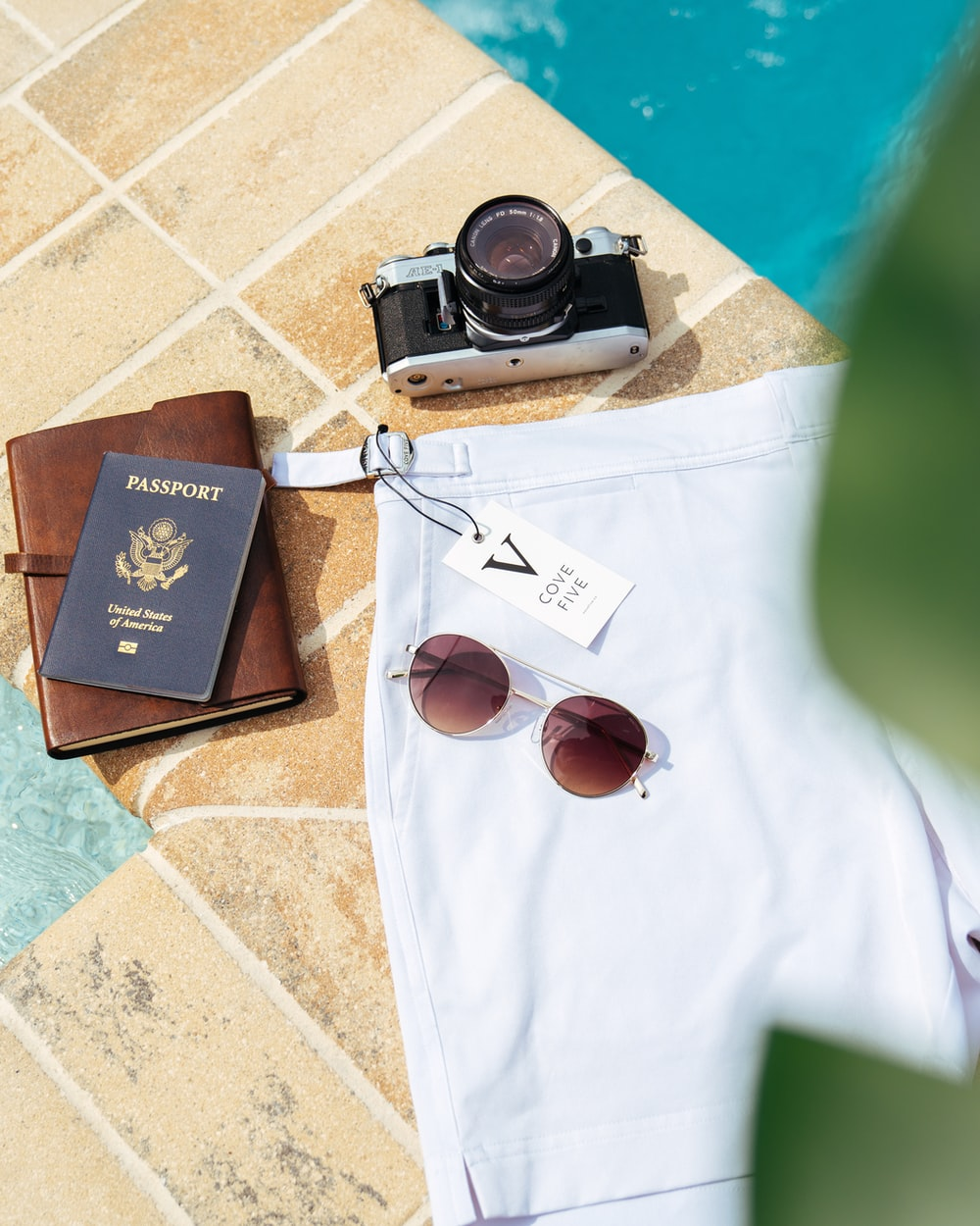 black and grey film camera, passport and white shorts on poll sside