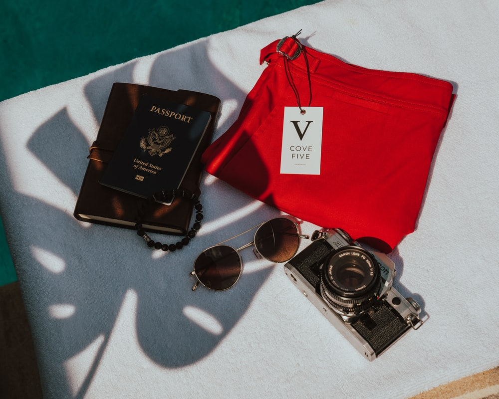 four passport, sunglasses, camera, and red bottoms on top of white textile