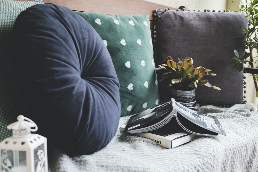 two books beside three assorted-color pillows