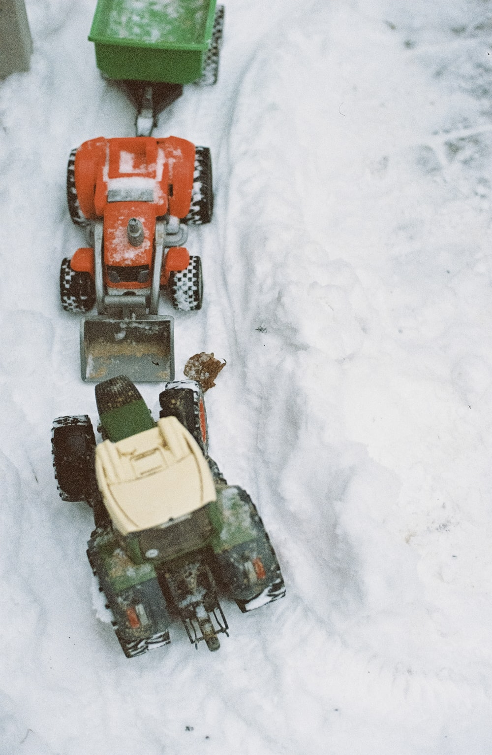 three red vehicle toys on snow