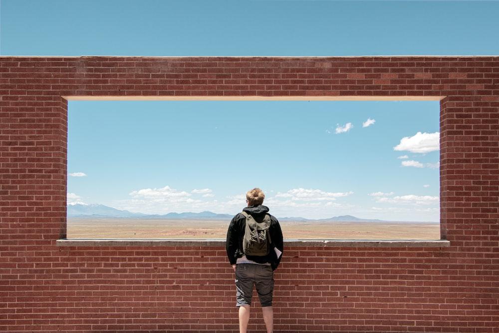 man standing on concrete brick wall