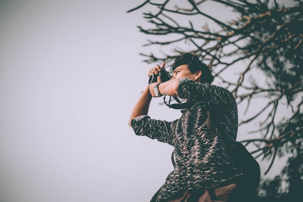 man taking photo near tree