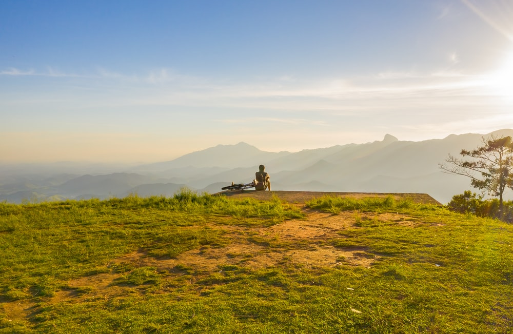 person sitting on cliff overlooking mountain during daytime