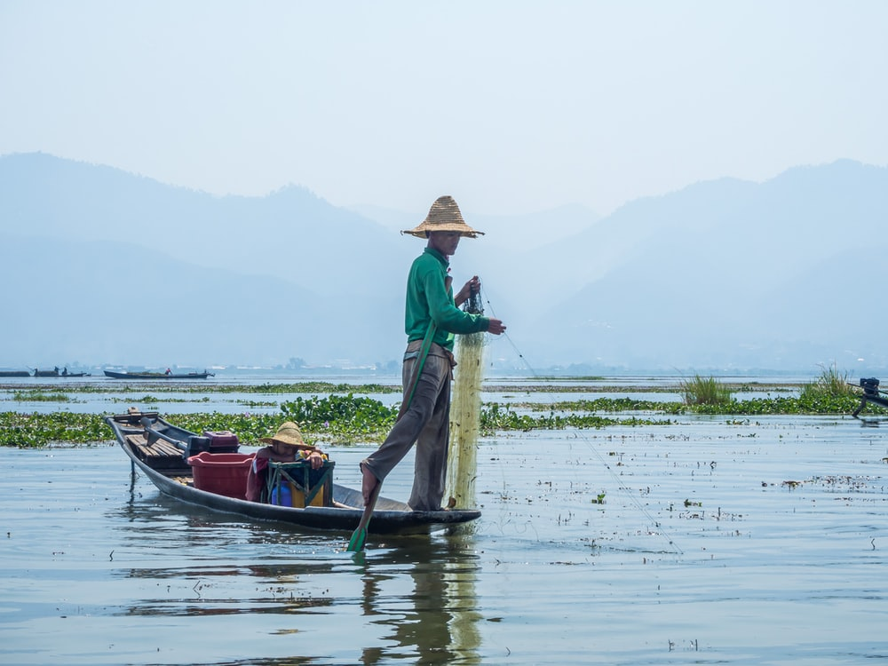 photography of man standing on brown boat during daytime