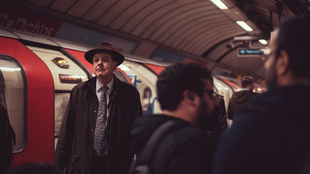 man in brown hat and coat near train