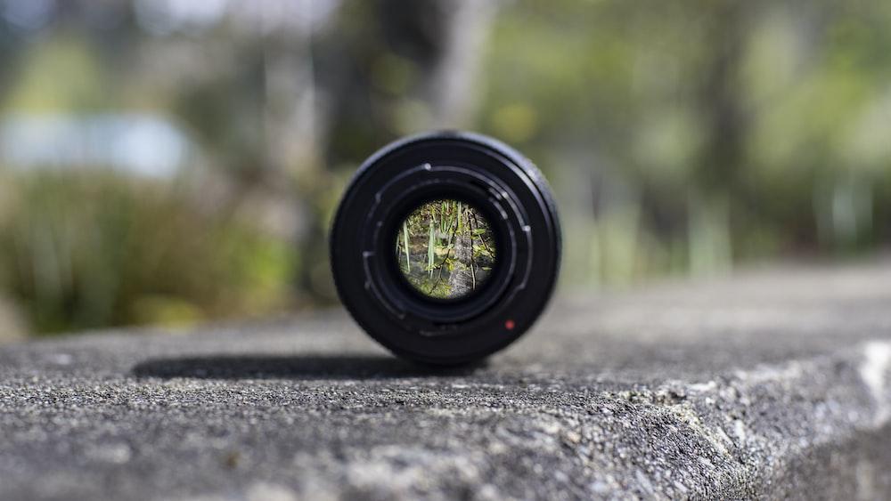 black DSLR camera lens on concrete surface