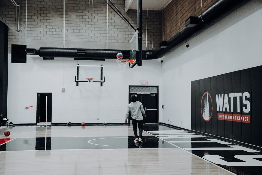 man standing inside basketball court looking at ball on basketball hoop