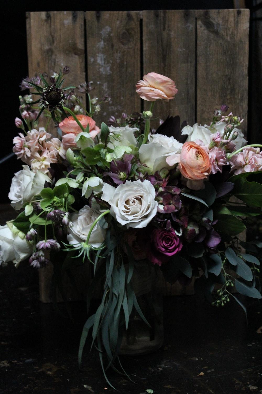 assorted-color flower arrangement in wooden pallet