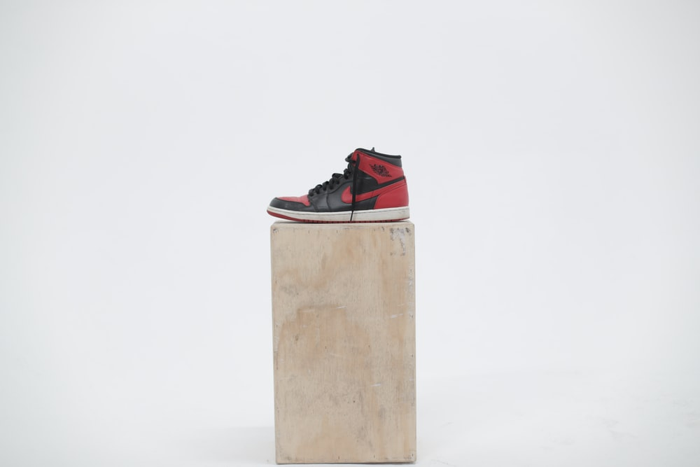 unpaired black and red Air Jordan 1 shoe on wooden box